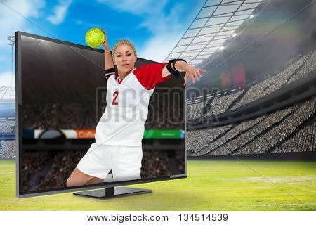 Sportswoman throwing a ball against view of a stadium