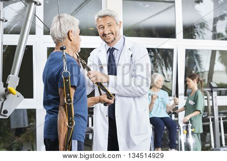 Happy Mature Doctor Assisting Senior Man With Resistance Band