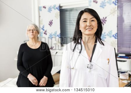 Confident Doctor Smiling While Patient Sitting In Background