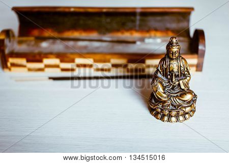 The statuette of the Buddha's blessing on a light background with Aromatic sticks.