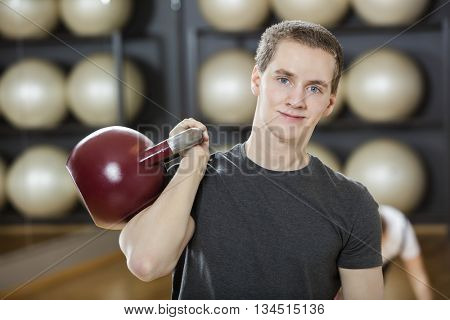 Attractive Young Man Exercising With Kettlebell In Gym