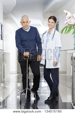 Confident Female Doctor With Senior Man Using Cane