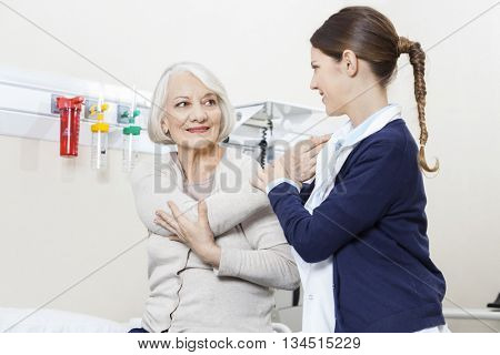 Physiotherapist Helping Smiling Senior Patient With Hand Exercis
