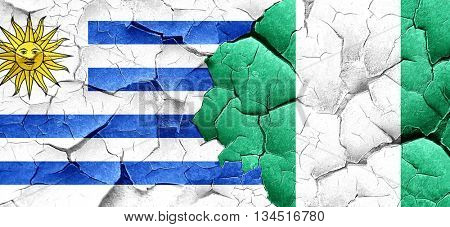 Uruguay flag with Nigeria flag on a grunge cracked wall