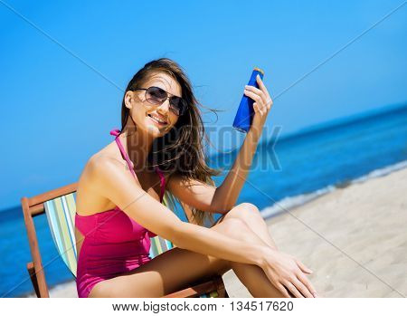 Beautiful, sporty and young woman in sexy swimsuit using sun tan cream on the beach