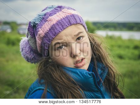 The sad girl in a knitted cap.