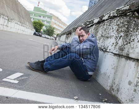 Sad Man sit near the Brick Wall