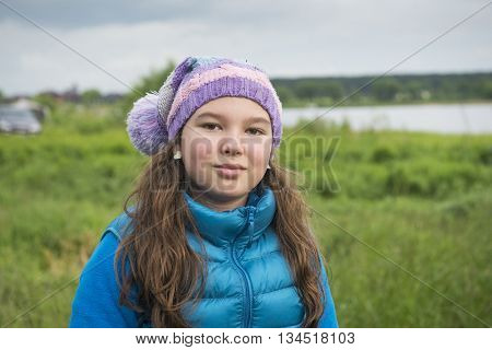 Girl in a knitted cap and demi-season jacket in nature