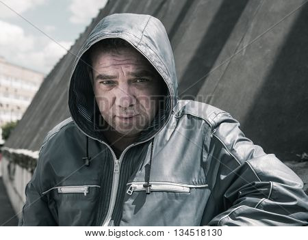 Upset man in a jacket with a hood. Street photography