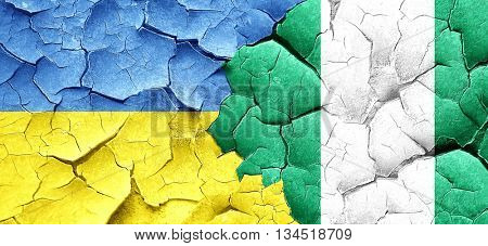 Ukraine flag with Nigeria flag on a grunge cracked wall