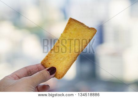 a piece of baked crispy butter bread in human hand
