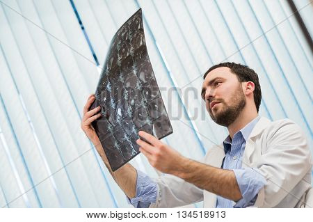 Portrait of doctor sitting in office holding xray image.