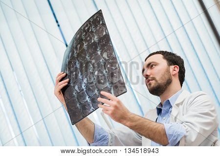 Portrait of a handsome caucasian male radiologist holding x-ray while sitting at his office.