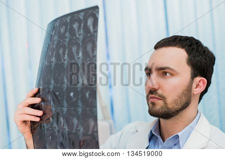 Doctor viewing MRI scans at his office.