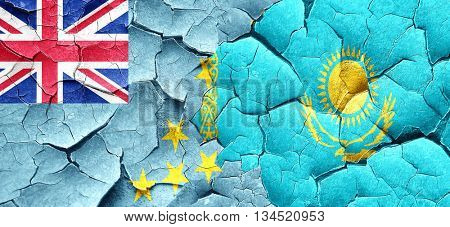 Tuvalu flag with Kazakhstan flag on a grunge cracked wall