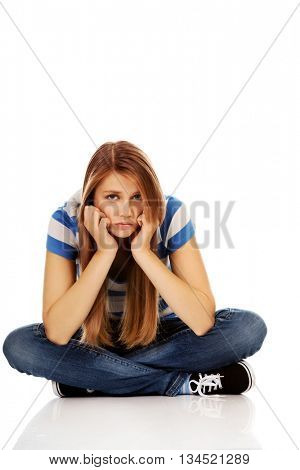 Teenage sad woman sitting on the floor