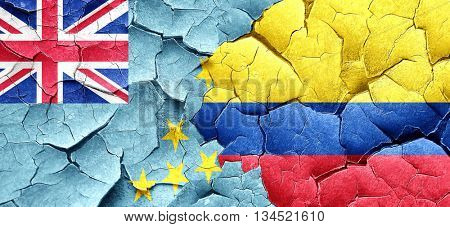 Tuvalu flag with Colombia flag on a grunge cracked wall