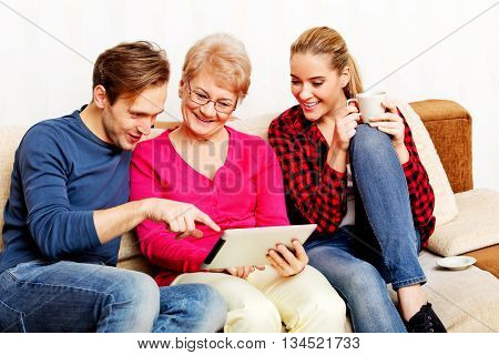 Young couple with old woman sitting on couch and watching something on tablet