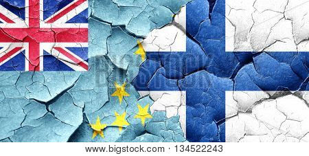 Tuvalu flag with Finland flag on a grunge cracked wall