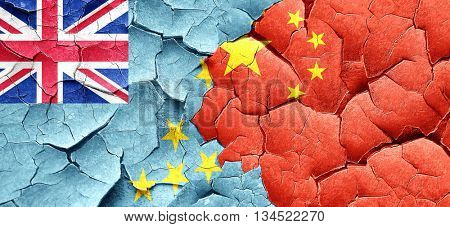 Tuvalu flag with China flag on a grunge cracked wall