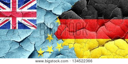Tuvalu flag with Germany flag on a grunge cracked wall
