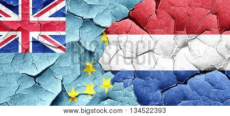 Tuvalu flag with Netherlands flag on a grunge cracked wall