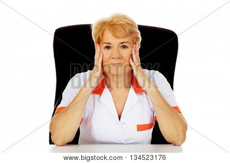 Elderly female doctor or nurse sitting behind the desk with headache