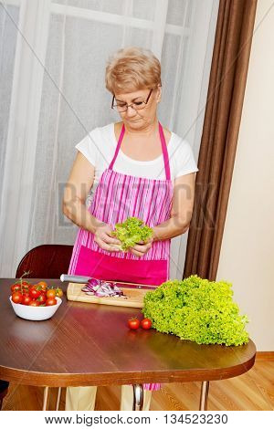 Senior woman tearing green lettuce