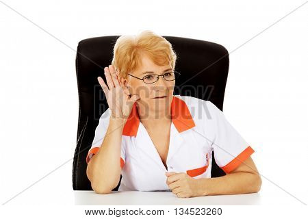 Smile elderly female doctor or nurse sitting behind the desk and overhears a conversation