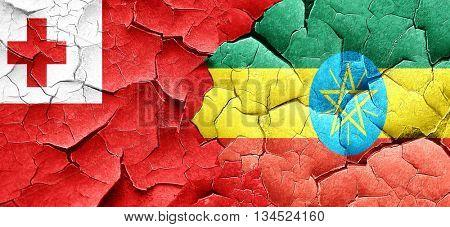 Tonga flag with Ethiopia flag on a grunge cracked wall