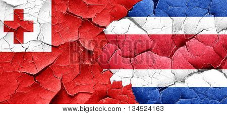 Tonga flag with Costa Rica flag on a grunge cracked wall