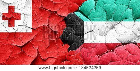 Tonga flag with Kuwait flag on a grunge cracked wall