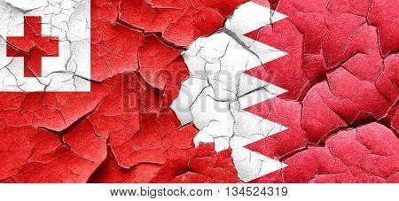 Tonga flag with Bahrain flag on a grunge cracked wall