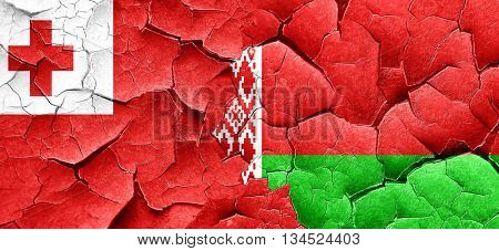 Tonga flag with Belarus flag on a grunge cracked wall