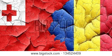 Tonga flag with Romania flag on a grunge cracked wall