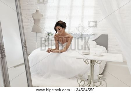 Happy bride daydreaming in bedroom, sitting on bed, looking at engagement ring.