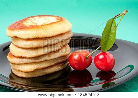 fritters on a plate with strawberries on a green background.