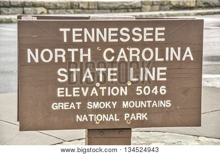 Brown and white sign in Great Smoky Mountains National Park marking the elevation and the Tennessee and North Carolina state lines