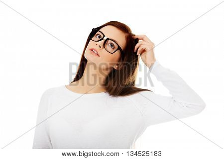 Young beautiful woman thinking looking up