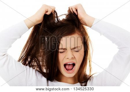 Young angry woman pulling her hair