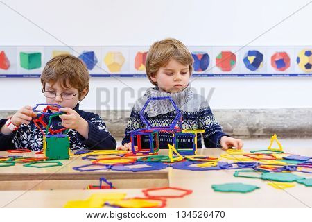 Two little children playing with lots of colorful plastic blocks kit indoor. kid boys having fun with building and creating geometric figures and learning mathematics.