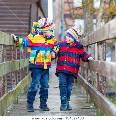 Two happy little kid sibling boys and friends in colorful clothes standing on bridge on spring day. Children having fun together, autumn or spring. Happy, joyful family