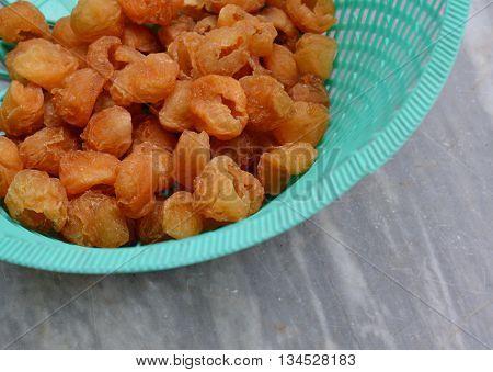 dry longan in the green plastic basket
