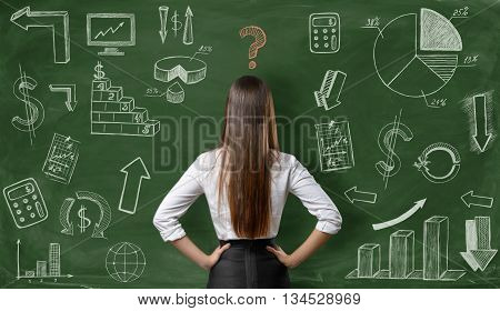 Back view of businesswoman with question mark over her head on green background with finance graphs. Confusion. Predicament. Financial and business concept. Economic and statistical graphs.