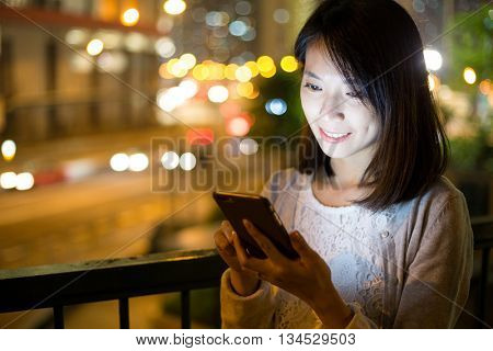 Asian woman using cellphone at night