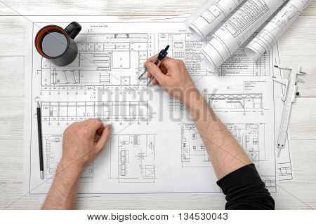 Close-up hands of man holding an engineering divider over drawing plan in top view. Workplace of architect or constructor. Engineering work. Construction and architecture. Architect drawing.