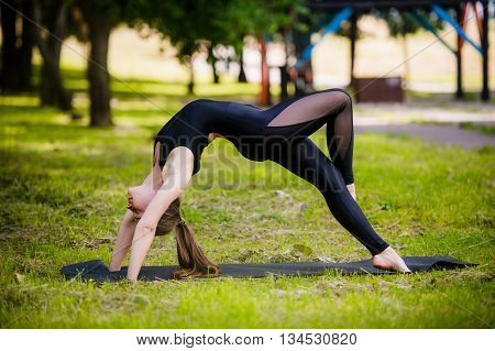 Pretty woman doing yoga exercises in the park.