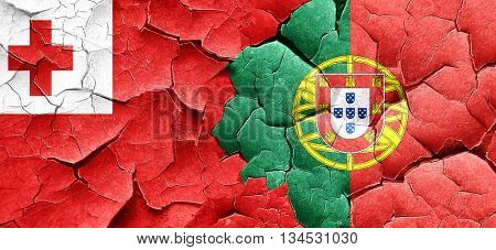 Tonga flag with Portugal flag on a grunge cracked wall