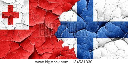 Tonga flag with Finland flag on a grunge cracked wall