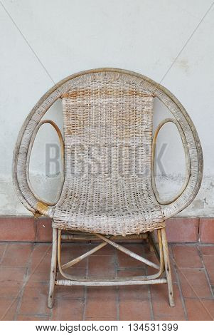 rattan chair on the white building wall